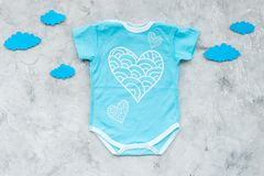 Newborn baby`s sleep concept. To put the child to bed. Baby bodysuit near clouds on grey background top view.  royalty free stock photos