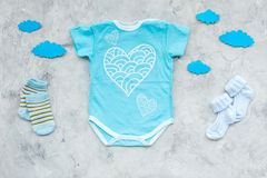 Newborn baby`s sleep concept. To put the child to bed. Baby bodysuit near clouds on grey background top view.  stock images