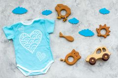 Newborn baby`s sleep concept. To put the child to bed. Baby bodysuit near clouds and toys on grey background top view.  stock photography