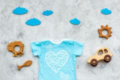 Newborn baby`s sleep concept. To put the child to bed. Baby bodysuit near clouds and toys on grey background top view.  royalty free stock photography