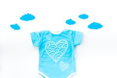 Newborn baby`s sleep concept. To put the child to bed. Baby bodysuit near clouds on white background top view.  Royalty Free Stock Photos