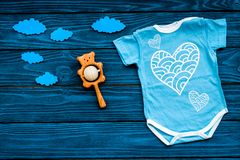 Newborn baby`s sleep concept. To put the child to bed. Baby bodysuit near clouds on blue wooden background top view copy. Newborn baby`s sleep concept. To put stock photography
