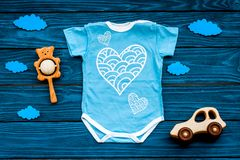 Newborn baby`s sleep concept. To put the child to bed. Baby bodysuit near clouds and cbaby accessories on blue wooden. Newborn baby`s sleep concept. To put the royalty free stock photography