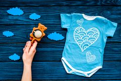 Newborn baby`s sleep concept. To put the child to bed. Baby bodysuit near clouds and cbaby accessories on blue wooden. Newborn baby`s sleep concept. To put the stock image