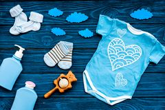 Newborn baby`s sleep concept. To put the child to bed. Baby bodysuit near clouds and cbaby accessories on blue wooden. Newborn baby`s sleep concept. To put the royalty free stock image