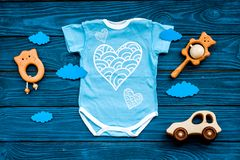 Newborn baby`s sleep concept. To put the child to bed. Baby bodysuit near clouds and cbaby accessories on blue wooden. Newborn baby`s sleep concept. To put the royalty free stock photos