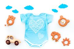 Newborn baby`s sleep concept. To put the child to bed. Baby bodysuit near clouds and cbaby accessories on white. Background top view royalty free stock images