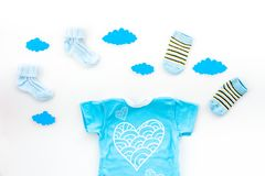Newborn baby`s sleep concept. To put the child to bed. Baby bodysuit near clouds and cbaby accessories on white. Background top view royalty free stock photo