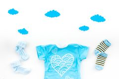 Newborn baby`s sleep concept. To put the child to bed. Baby bodysuit near clouds and cbaby accessories on white. Background top view stock photo