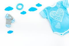 Newborn baby`s sleep concept. To put the child to bed. Baby bodysuit near clouds on white background top view copy space. Newborn baby`s sleep concept. To put stock photography