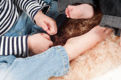 Newborn baby and sister foot Stock Photos