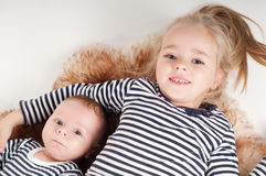 Newborn baby with sister in striped clothes Stock Photos