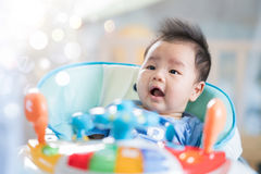 Asian baby smile on toy car. Newborn baby sit on walking training car, Asian baby smile on toy car Stock Photography