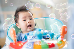 Asian baby smile on toy car. Newborn baby sit on walking training car with bubble soft, Asian baby smile on toy car Royalty Free Stock Photo