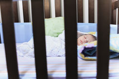 Newborn baby sleep in a crib Stock Images