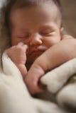 Newborn baby sleeping. Close up of newborn baby sleeping cuddled in a soft warm blanket Stock Image