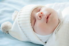 Newborn baby sleeping. A newborn baby boy is sleeping on blue blanket and wearing a hat Stock Image