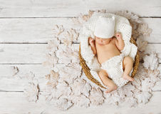 Newborn baby sleeping in basket on leaves over white. Wooden background Stock Photography