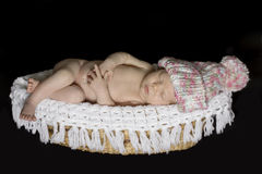 Newborn Baby Sleeping on Basket wearing hat Stock Photography