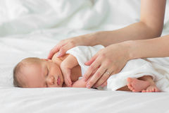 Newborn baby sleeping on a blanket. Mother gently strokes her child`s hand Royalty Free Stock Image