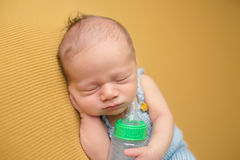 Newborn Baby Sleeping with Bottle stock image