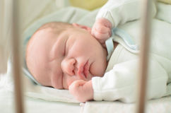 Newborn baby sleeping in crib Stock Photos