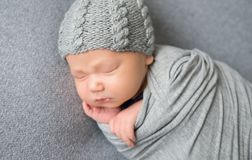 Newborn baby sleeping curled up in grey blanket. Beautiful newborn baby sleeping curled up in grey blanket and wearing grey hat. Little baby lying on grey royalty free stock image