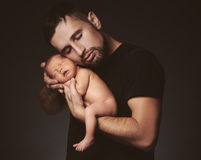 Newborn baby sleeping in his arms of father on dark Stock Photography