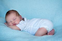 Newborn baby sleeping on his tummy full length side profile blue background. Cute stock photography
