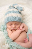 Newborn Baby Sleeping in Knit Hat Stock Image