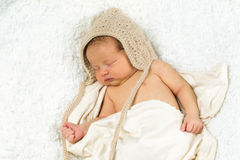 Newborn Baby Sleeping with knitted Hat on. Royalty Free Stock Photo