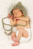 Newborn Baby Sleeping with knitted Hat on. Stock Images