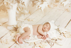 Newborn baby sleeping on leaves over white wooden  Royalty Free Stock Image