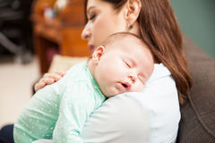 Newborn baby sleeping with mom. Portrait of a cute newborn baby girl sleeping on her mother's shoulder at home Stock Image