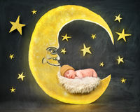 Newborn Baby Sleeping on Night Star. A little newborn baby is sleeping on a paper cutout of a yellow moon with stars in the background for a bedtime or sleep royalty free stock images