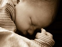 Newborn baby sleeping peacefully. Peaceful closeup image of newborn infant sleeping on his first day home, sepia tint. Good for Mother's Day, right to life royalty free stock photos