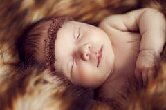 Newborn baby sleeping peacefully on the red fur Royalty Free Stock Image