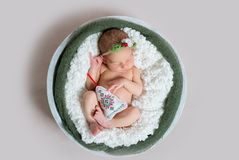 Newborn baby sleeping in round bowl, top view. Newborn baby girl with flower wreath and emroidered Christmass tree toy sleeping in round bowl covered with soft Royalty Free Stock Photos