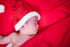 Newborn baby sleeping on santa het and red background stock image