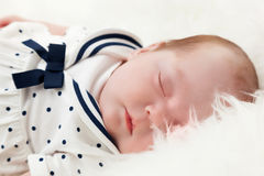 Newborn baby sleeping on white fur blanket. Wearing sailor dress. Royalty Free Stock Images