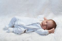 Newborn baby sleeping on white fur in sunlight