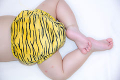 Newborn baby sleeping on white. rear view. butt in a diaper in leopard coloring diaper in bed, with a adorable crossed legs and fe Royalty Free Stock Image