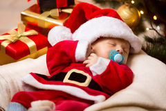 Newborn baby sleeping in white and red Santa Claus costume Stock Photography