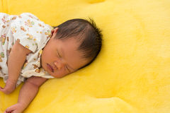 Newborn baby sleeping on yellow fur fabric bed. Stock Image