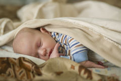Newborn baby sleeps in the crib. Newborn baby sleeps under dealcom Royalty Free Stock Photo