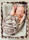 A newborn baby sleeps in a drawer wrapped in a knitted brown sca Royalty Free Stock Photo