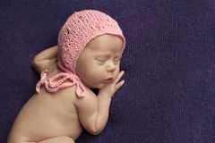 A newborn baby sleeps on a lilac plaid royalty free stock photography
