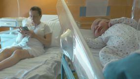 Newborn baby sleeps in a medical baby cradle. A young mother after giving birth lies on the hospital cot and looks into the phone on the background. Cute stock footage