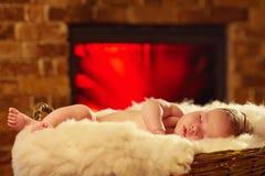 Newborn baby sleeps near the fireplace Royalty Free Stock Photo