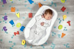 Newborn baby sleeps in a special orthopedic mattress Baby cocoon, on a wooden floor multicolored letters around. Calm. Newborn baby quietly sleeps in a special royalty free stock photos